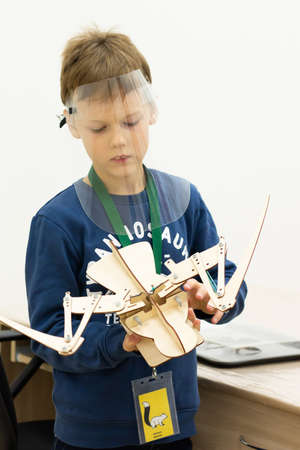 Boy wearing a protective screen with a movable wooden mock-up of a bird skeleton at a children's science event during the coronavirus pandemic