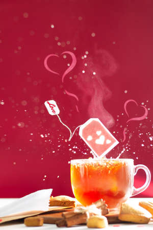 Tea bag with hearts and inscription Love on label above tea mug with splashes and heart shaped steam on dark red background. Copy space