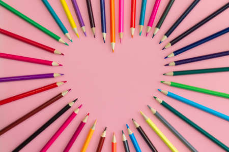 Heart laid out with sharpened multi-colored pencils on a pink background. Flat lay. Copy space.