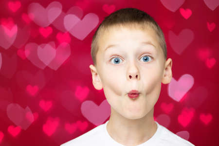 Boy teenager 7-10 in white t-shirt makes faces depicting kiss, with wide open eyes on red and pink hearts bokeh