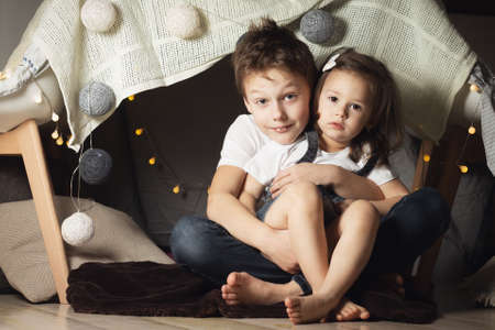 Siblings hug in hut of chairs and blankets. Brother and sister playing at home Standard-Bild