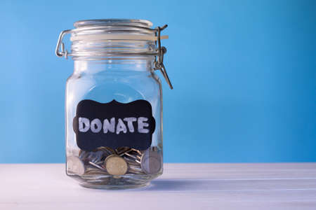 Glass jar with coins with chalk tag Donate on a blue background, donation and charity concept. Copy space.