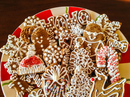 Holiday gingerbread cookies decorated with white icing and red sprinkles on a red and white candy cane striped holiday plate Stock Photo