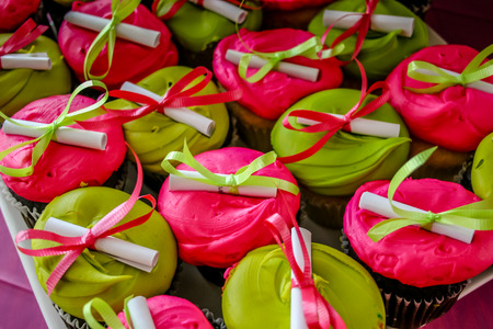 Bright pink and green cupcakes adorned with tiny diplomas tied with ribbons