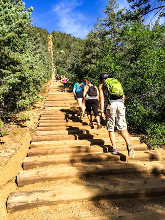 to incline: Hikers climbing up the Manitou Incline in Manitou Springs, Colorado on a sunny blue sky day Stock Photo