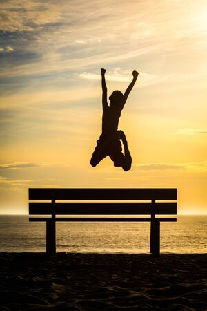 Happy child jumping and playing on the beach with a beautiful sunset in France on the Atlantic coast