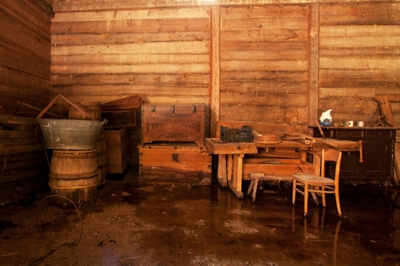 hunter's cabin: boxes, barrels, table, chairs standing in a wooden barn