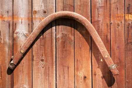 old horse harness on the wooden door to the barn