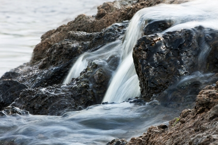 curiously: blue water overflowing by curiously shaped rocks Stock Photo