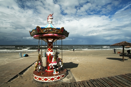 small, colorful carousel placed directly on the shore of the blue, lovely sky in the background