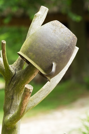 superimposed: old iron rusty pot superimposed on a wooden stick branched