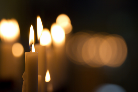 christian halloween: Burning wax candles in an old dark church with a blurred background