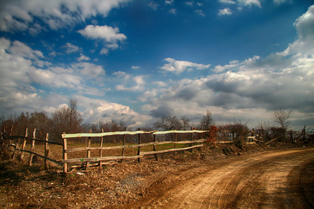Dirt road, old fence with poles and white clouds against the background of the dark blue sky