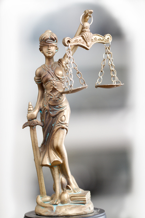 Statuette of justice goddess Themis against a light background