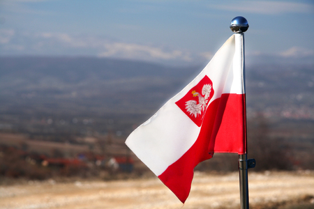 Polish flag with an eagle waving in the breeze against the background of mountains