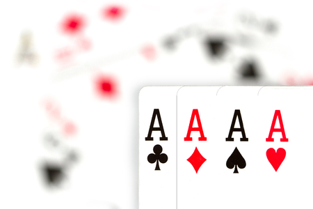 four aces against scattered, blurred cards Stock Photo