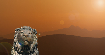 Monumental sculpture of a lion with orange mountains in the background