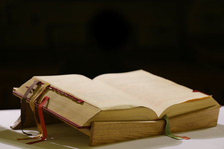 Liturgical book with colored tabs lying on a wooden stand on a white tablecloth