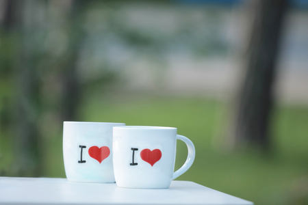 Two white cups with red hearts standing on a table in the garden