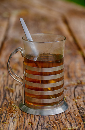 Outside, on an old wooden table stands a glass in a tea holder