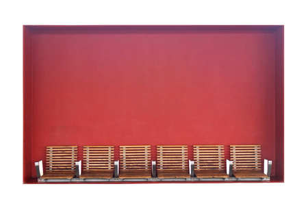 Wooden seats mounted in a wall niche with a red background