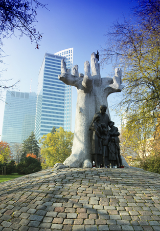 A tree-shaped statue with broken bones of Janusz Korczak in Warsaw against the background of modern buildings