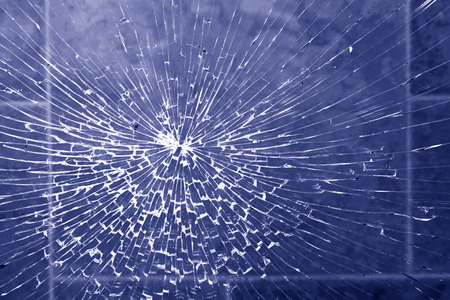 Radially cracked glass from impact in blue colors Stock Photo