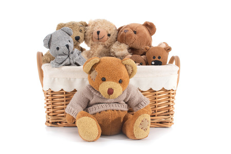 Teddy bears in a straw basket on a white background