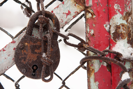 old padlock covered with hoarse frosted on a chain on a paint-smeared gate Banco de Imagens