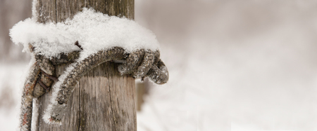 coastal wooden stake with nail nailed and covered with fresh snow