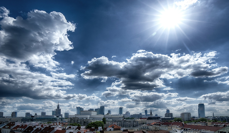 Panorama of Warsaw with dark clouds and sun