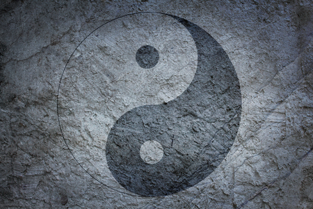 Chinese yin yang sign on a background of a concrete surface