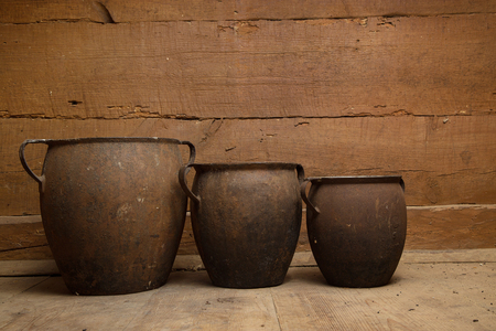 Large, old cast-iron cooking pots standing on a wooden floor against the background of a wooden wall.