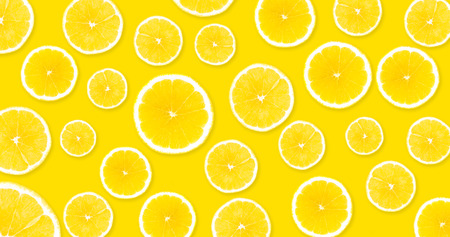 Background with yellow lemons from which you can see a yellow, uniform background