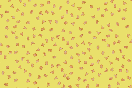 Small cookies, crackers of various shapes on a yellow background