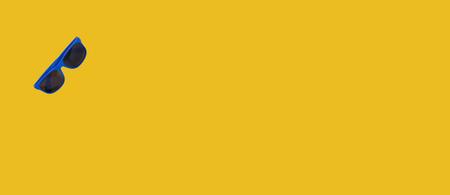 Blue sunglasses lying on a yellow like seaside sand background 写真素材