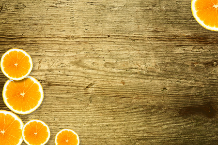 Slices of orange lying on a wooden background 写真素材