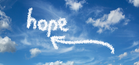HOPE inscription painted with clouds on a blue background with white clouds with arrows