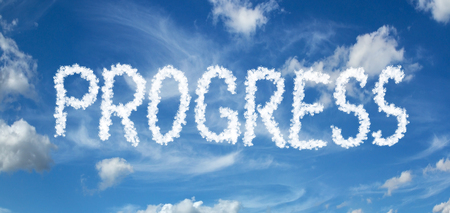 PROGRESS inscription painted with clouds on a blue background with white clouds 写真素材