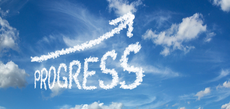 PRORESS sign with clouds painted on a blue background with white clouds with arrows