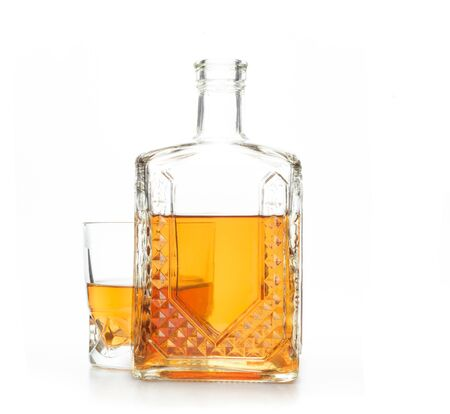 A crystal carafe and a glass of whiskey on a white background 写真素材