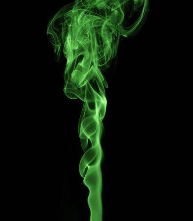 Green, twisted smoke on a black background 写真素材
