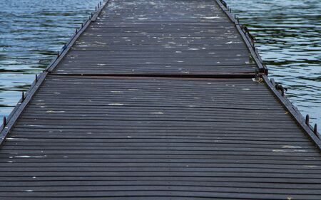 A wooden, slightly dilapidated bridge surrounded by water on both sides 写真素材 - 126663529