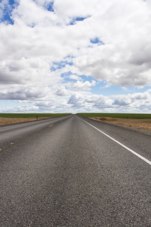 going nowhere: Open road going to nowhere with a big cloudy sky  Stock Photo