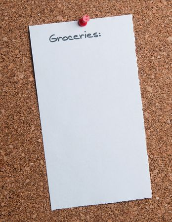White paper grocery list attached to a cork board.