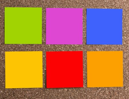 Multicolored adhesive notes attached to a cork board background. Reklamní fotografie