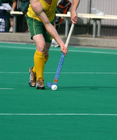 A player dribbles the ball in a hockey match photo
