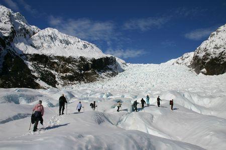 A group hikes up fox glacier - New Zealand. Stock Photo