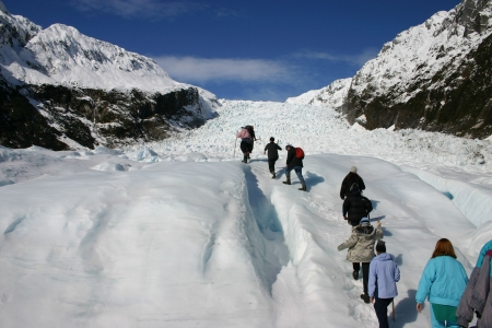 fox glacier: A group hikes up fox glacier - New Zealand. Stock Photo