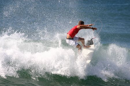 busts: A surfer busts the tail of his surfboard out of the wave. Stock Photo